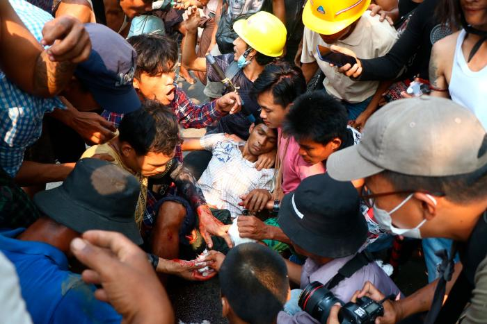 Protesters surround an injured man in Hlaing Tharyar township in Yangon, Myanmar, March 14, 2021.