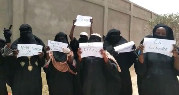 "A screenshot of a video showing women demonstrating on March 27, 2021 in N'Djamena, Chad's capital, holding signs saying, among others, ""We Want Justice"" and ""Freedom"", ""Idi out""."