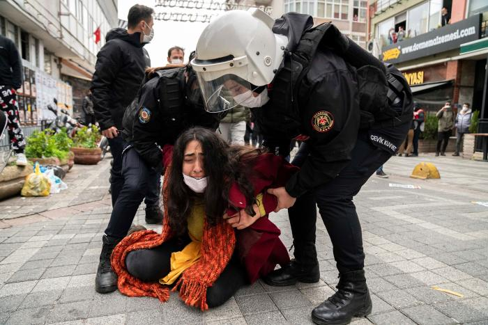 Police forcefully detain a protester  who is crying on the ground while the police stand over her at a demonstration.