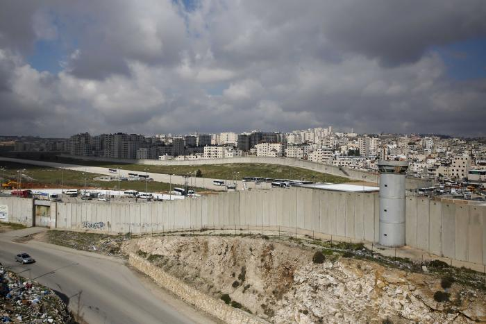 A concrete wall separates a city and a highway