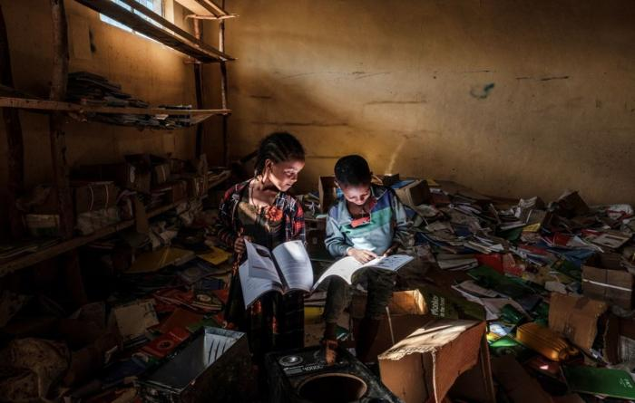Children look at books in an elementary school in the village of Bisober, Tigray on December 9, 2020. The school was occupied by Tigray Special Forces and also damaged after fighting broke out between Ethiopian and Tigray forces in November 2020.