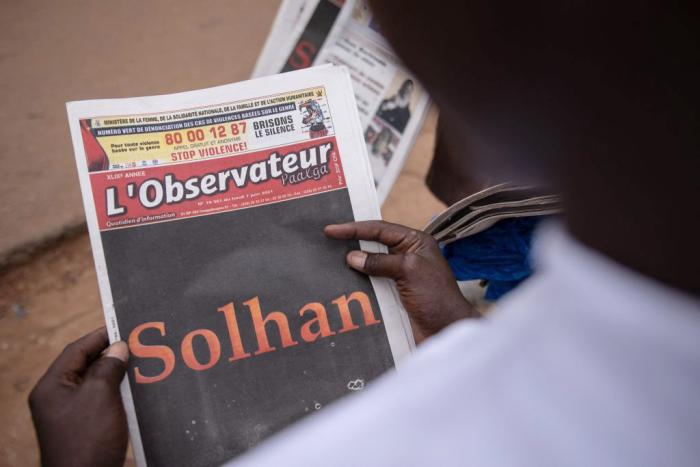 A man reads the L'Observateur Paalga newspaper in Ouagadougou on June 7, 2021, about the attacks that happened in Solhan.