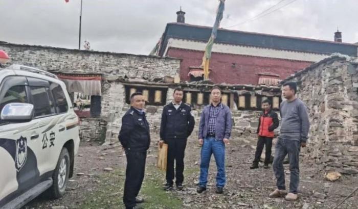 Flanqué de deux policiers, Zhang Ling, directeur du Bureau de la sécurité publique du comté de Tingri au Tibet (au centre de la photo) a mené une «visite d'inspection» au monastère de Tengdro près du village de Shekar, le 2 juillet 2020.