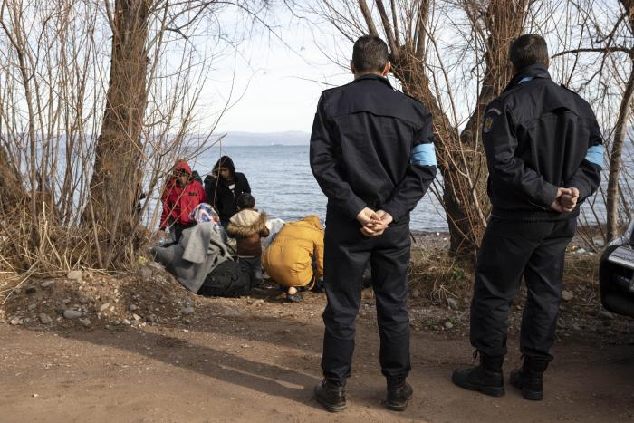 Frontex border officers stand near migrants on the island of Lesbos, Greece, on March 2020.