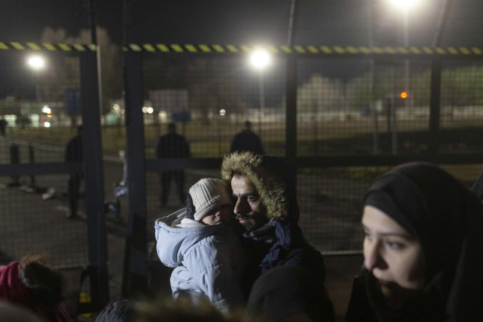 A man holds a child close to a border crossing between Serbia and Hungary, Kelebija, Serbia, Thursday, February 2020.