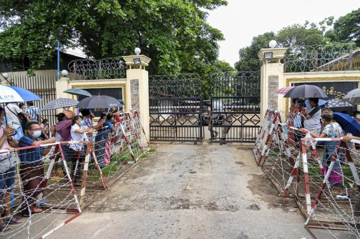 People stand outside the gates of a prison