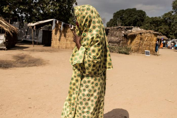"""A woman walks through the Internally Displaced Person camp""""25 de junho,""""in Metuge, Mozambique on May 20, 2021."""