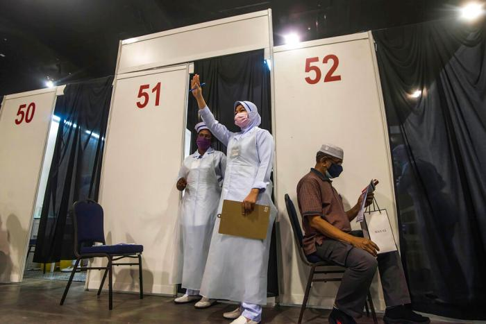 A health worker gestures to the next vaccine recipient at Malaysia International Trade & Exhibition Centre in Kuala Lumpur, Malaysia on May 31, 2021.