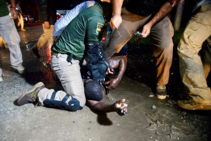 Agents of the National Migration Institute detain a migrant during an operation to halt the progress of a caravan of migrants and asylum seekers in Chiapas state, Mexico on September 1, 2021.