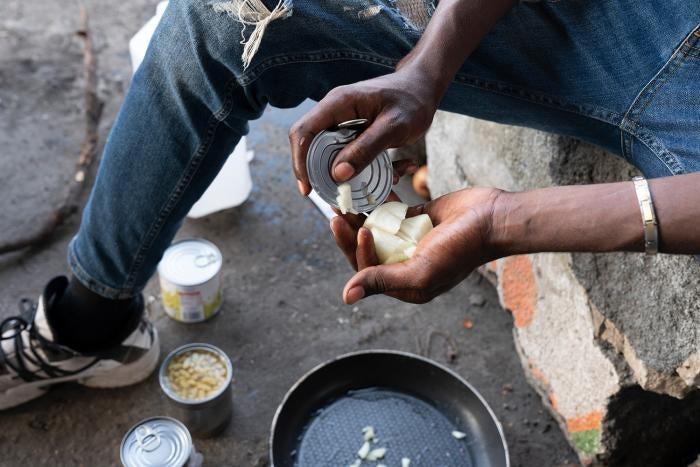 Un garçon malien de 17 ans émince des oignons au moyen d'un couvercle de boîte de conserve, juillet 2021, Calais (France).