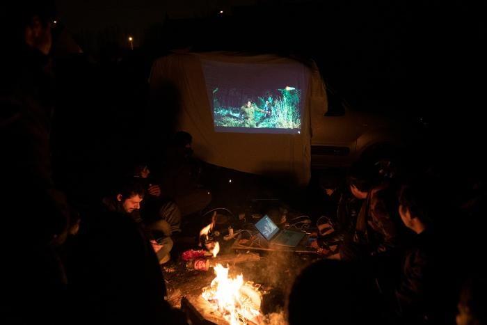 Un groupe de garçons et de jeunes hommes afghans regardent un film projeté par un bénévole dans leur campement de la banlieue de Calais (nord de la France) en septembre 2020.