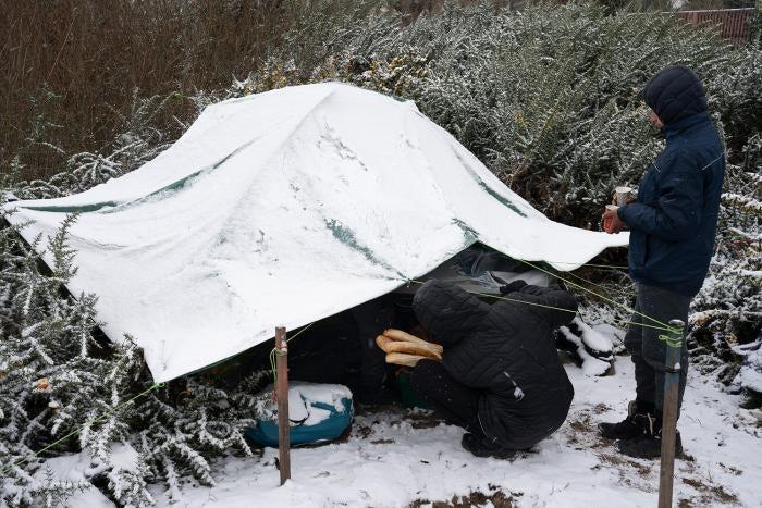 Des bénévoles distribuent de la nourriture et du thé à un groupe de garçons afghans dans un campement de migrants à Calais (nord de la France) en février 2021.