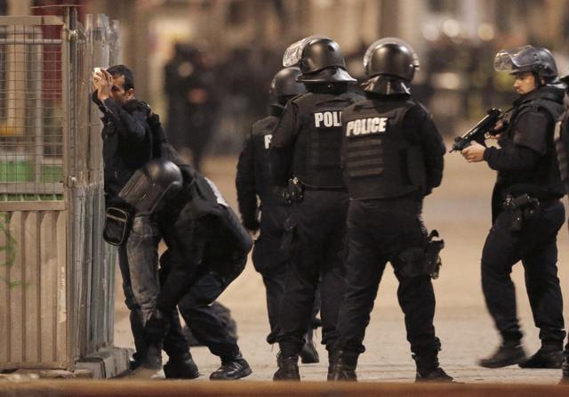 French police stop and search a local resident during an operation in Saint-Denis, France.