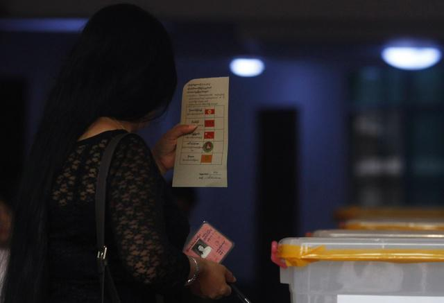 A woman holds a ballot slip and her national identity card before casting her vote at a polling station during by-elections in Burma on April 1, 2012.