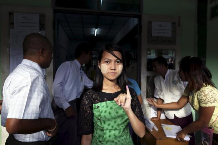 A woman shows her inked finger after casting her ballot during general elections in Rangoon on November 8.