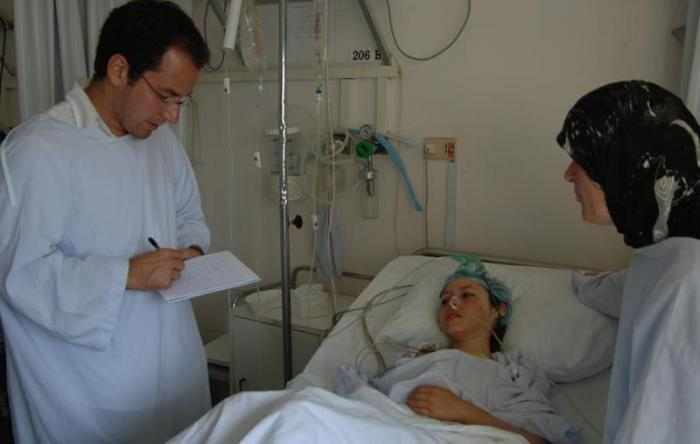 Nadim Houry (left) interviews a civilian casualty in Lebanon.
