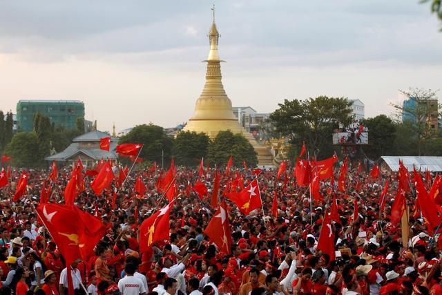Supporters wave NLD flags after Aung San Suu Kyi gave a speech at her campaign rally in Rangoon.