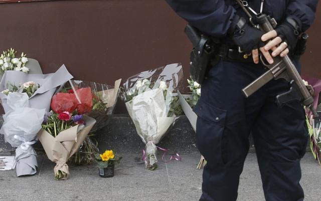 A policeman stands guard outside the Le Carillon restaurant the morning after a series of deadly attacks in Paris
