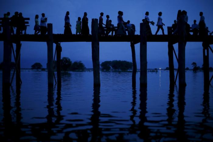 People cross the U Bein bridge in Mandalay, Burma on Oct. 6, 2015.