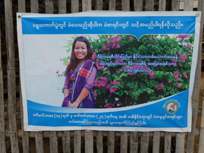 A Union Elections Commission voter awareness poster on a fence lining the road near Nyaung Shwe, Southern Shan State.