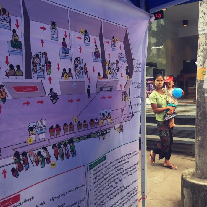 A woman walks by a voter education booth in downtown Rangoon.