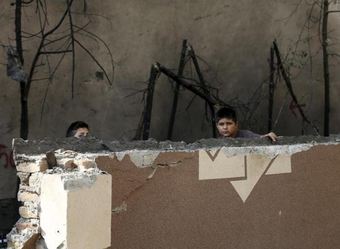 Afghan boys look out from behind a damaged wall after a Taliban attack in Kabul, Afghanistan October 6, 2015.
