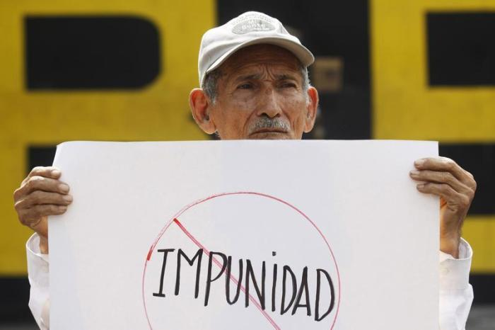 "A man holds a banner that reads ""impunity"", during a protest outside the Special Military Security Unit base in San Salvador, August 24, 2011."