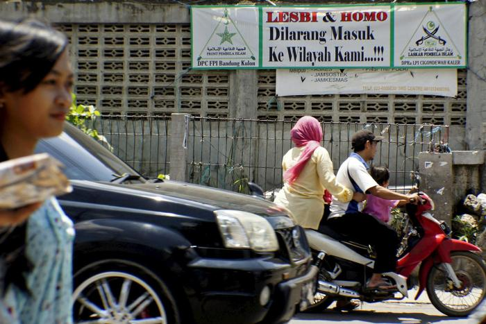People drive a motorcycle past a banner put up by the hardline Islamic Defenders Front calling for gay people to leave the Cigondewah Kaler area in Bandung, Indonesia West Java province, January 27, 2016 in this photo taken by Antara Foto. Indonesia's thi