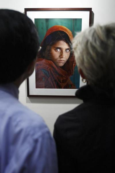 "Visitors look at the ""Afghan Girl"" photo during U.S. photographer Steve McCurry's exhibition at the Asian Civilisation Museum in Singapore June 26, 2009."