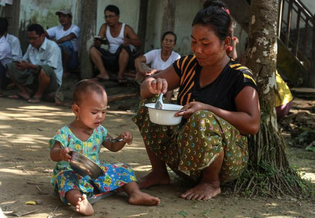 A woman who fled from recent violence in Maungdaw feeds her daughter at a monastery used as a temporary internally displaced persons (IDP) camp in Sittwe, Burma on October 15, 2016.