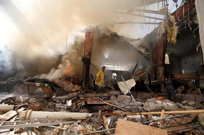 Firefighters try to extinguish a fire at the community hall in Sanaa where Saudi-led coalition warplanes attacked a funeral on October 8, 2016.
