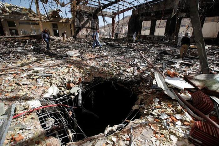 Journalists and police inspect the scene at the community hall in Sanaa that Saudi-led coalition warplanes attacked on October 8, 2016.