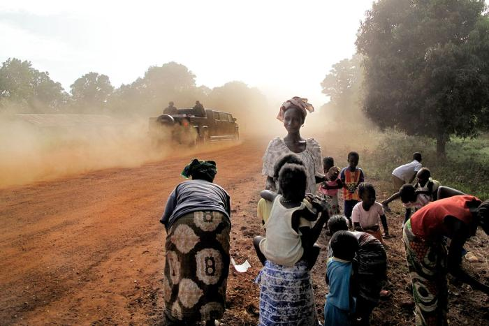 Gambia's President Jammeh's Hummer passes a group of women and children on January 25, 2014 in the Gambian village of Killin.