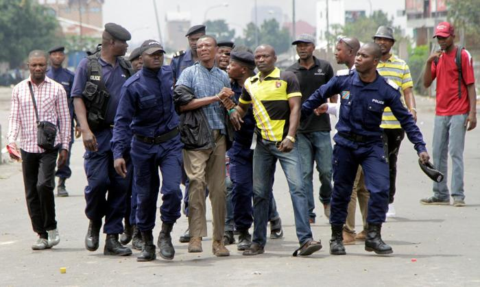 Congolese policemen arrest opposition activists participating in a march to press President Joseph Kabila to step down in the Democratic Republic of Congo's capital, Kinshasa, September 19, 2016.