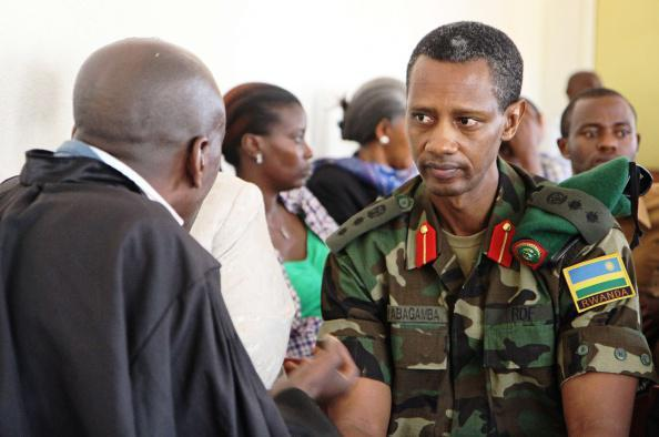Col. Tom Byabagamba speaking to his lawyer before his hearing at the military court in Kigali on August 29, 2014.