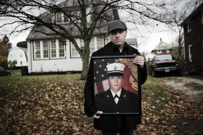 Gary Noling holding a photo of his daughter Carri Goodwin, a rape victim who died of acute alcohol intoxication less than a week after receiving an Other Than Honorable discharge from the Marines.