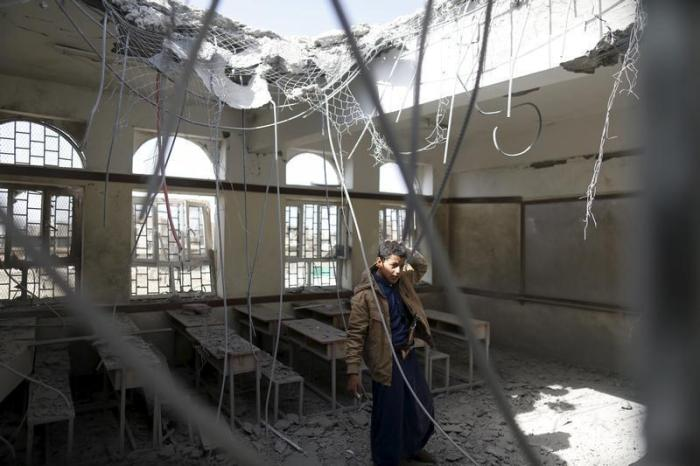A boy stands in a classroom at his school after it was hit by a Saudi-led air strike in Yemen's capital Sanaa July 20, 2015.