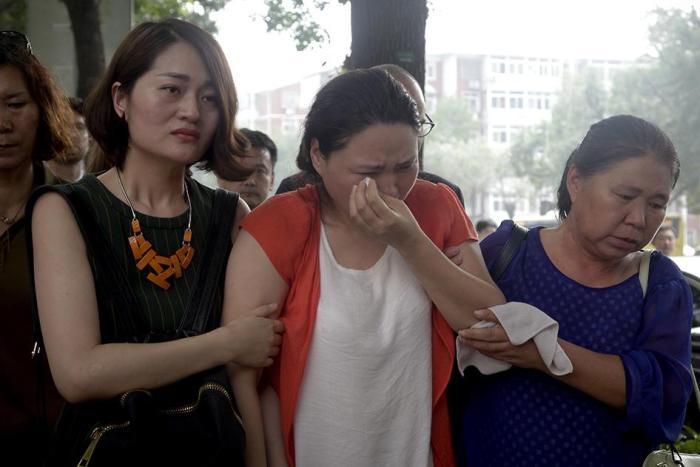 Fan Lili, the wife of imprisoned activist Gou Hongguo, is escorted by Li Wenzu, the wife of imprisoned lawyer Wang Quanzhang, and another woman as they stage a protest outside the Tianjin No. 2 Intermediate People's Court in Tianjin, China on Monday, Augu