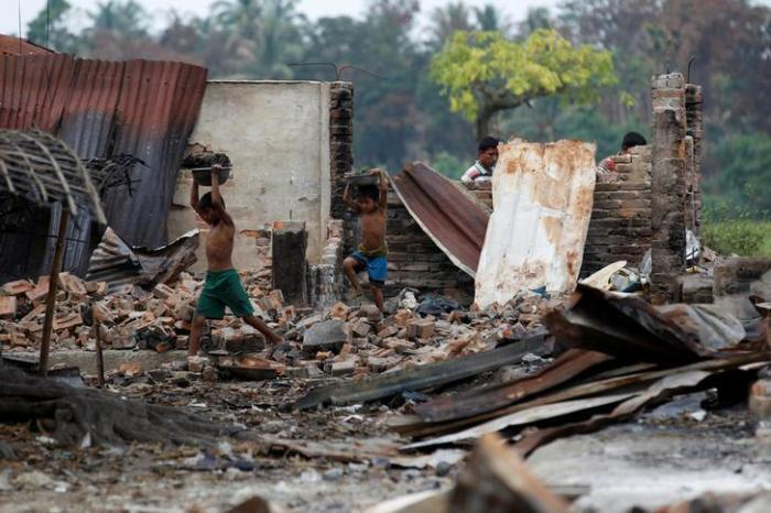 Children recycle goods from the ruins of a market which was set on fire at a Rohingya village outside Maungdaw in Rakhine state, Burma, on October 27, 2016.