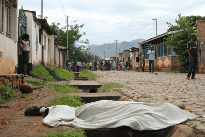 Residents outside their houses in Nyakabiga, in the Burundian capital Bujumbura, look at the body of a man shot dead on December 11, 2015.
