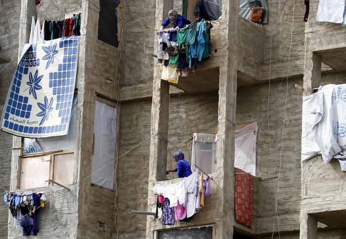 Syrian women hang clothing on their balconies inside a compound for Syrian Refugees in Sidon, south Lebanon April 17, 2015.
