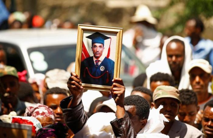 A man at a funeral holds up the portrait of Tesfu Tadese Biru, 32, a construction engineer who died during a stampede after police fired warning shots at an anti-government protest in Bishoftu during Irreecha, the thanksgiving festival of the Oromo people