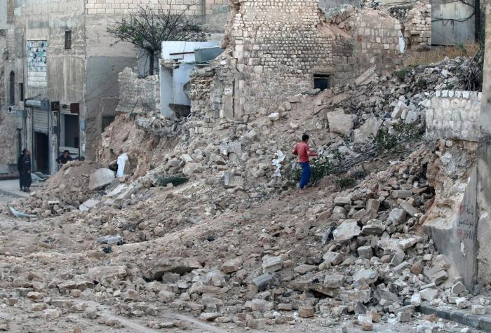 A civilian collects tree branches from the rubble of a damaged site in Aleppo's rebel-held besieged Qadi Askar neighbourhood.