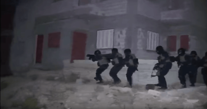 Still from a video published by the Egyptian Interior Ministry. The video shows commandos stealthily approaching a building. But military experts said the bright, white light illuminating the commandos during their approach was one indication that the rai