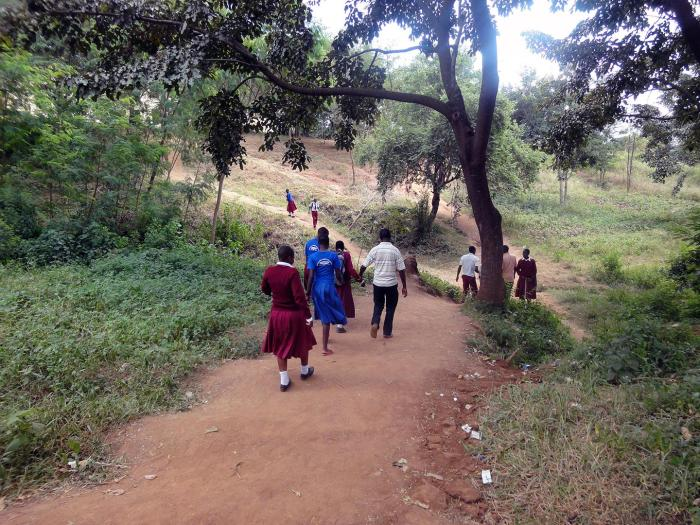 Female students who are blind, are guided down a steep and slippery hill by their teachers. They have to walk through rough terrain to get from their secondary school to their school's hostel in Mwanza city.