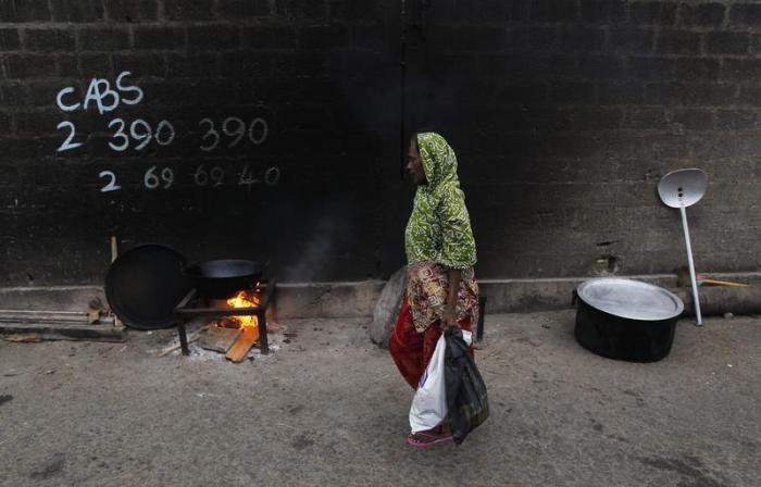 A woman walks past a cooking fire along a road during Eid al-Fitr in Colombo, Sri Lanka, August 8, 2013.