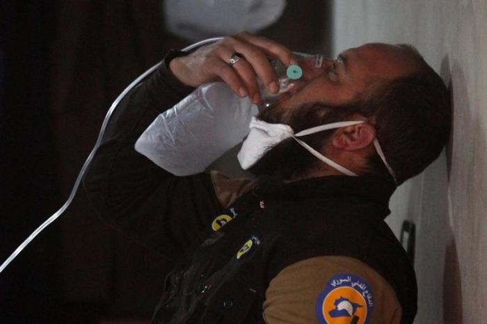 A civil defense member breathes through an oxygen mask, after what rescue workers described as a suspected chemical attack in the town of Khan Sheikhoun in rebel-held Idlib, Syria April 4, 2017.