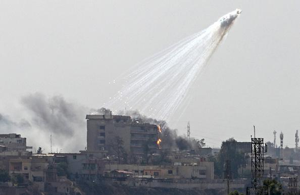 Photo of smoking and burning white phosphorus streaking to the ground in west Mosul on June 2, 2017.