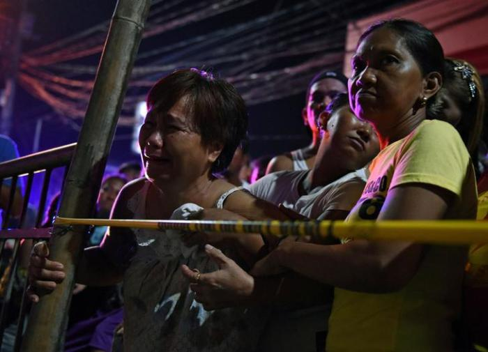 A victim's relative cries behind the police line at the site of a drug-related shooting in metro Manila, Philippines, June 19, 2017.
