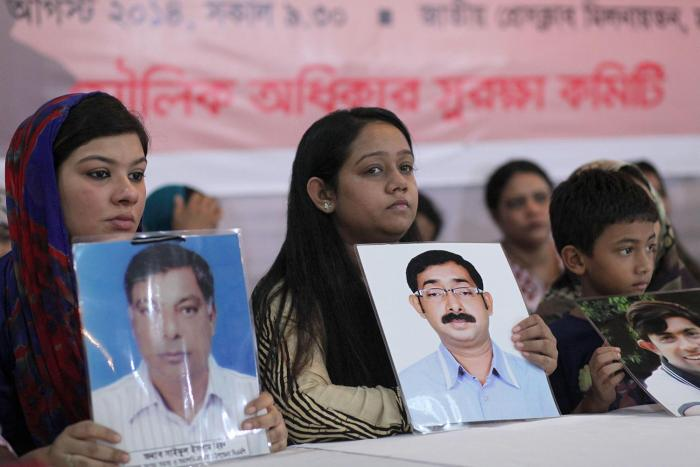 Relatives hold portraits of disappeared family members at an event calling for the end of enforced disappearances, killings, and abductions, in Dhaka, Bangladesh, August 30, 2014.